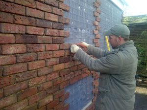 Builder applying brick slips to an ICF wall