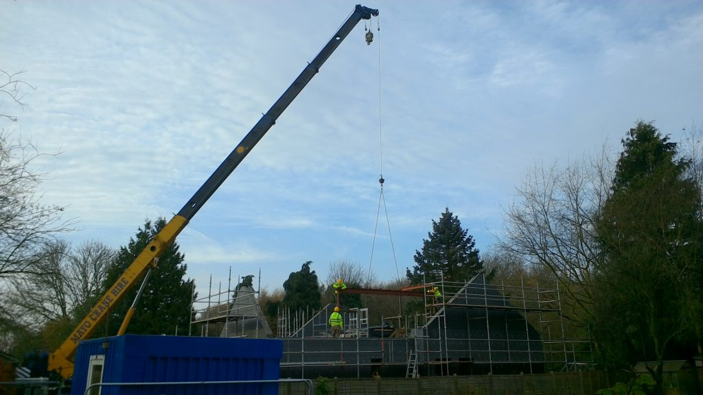 Large crane lifting steel beams onto house