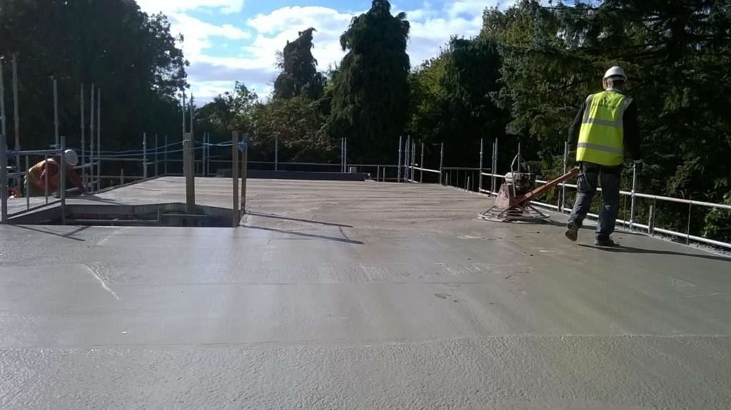 Metal deck floor being power floated on a garden building plot self-build in Lincolnshire